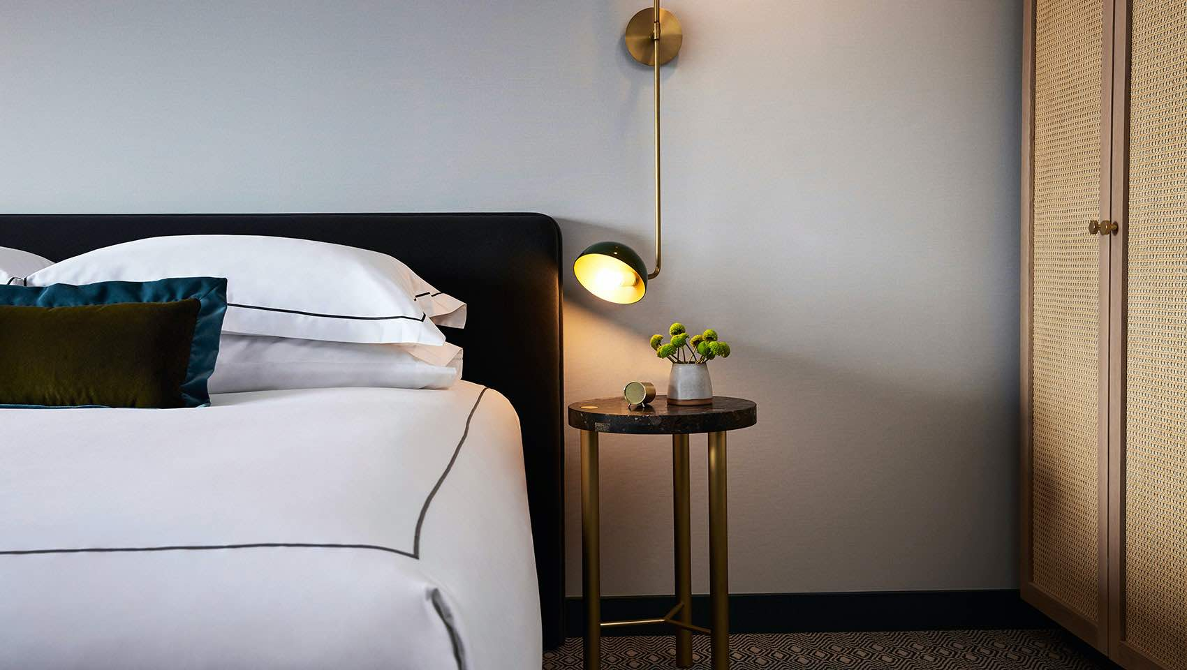 Kimpton Saint George Hotel bedroom with bed and side table